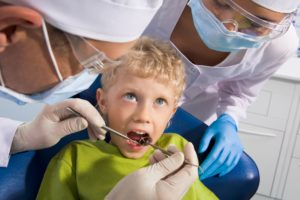 Image of dental examining being given to little boy by dentist and his assistant